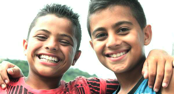 Two boys smiling with arms around one another