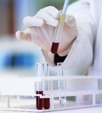 A photo of a lab technician testing a blood sample