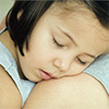 Un niño que duerme en los brazos de un padre