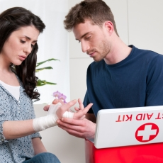 A photograph of a man administering first aid to a woman