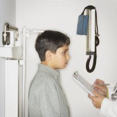 Fotografía de un doctor midiendo la estatura de un niño