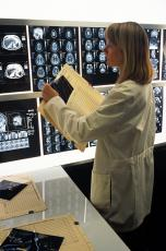 Photograph of a female health professional looking at brain images