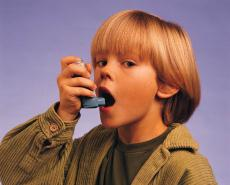 Photograph of a young boy using an inhaler