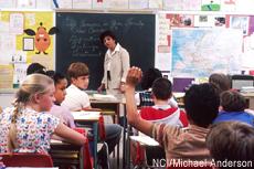 Fotografía de una maestra y unos estudiantes en el aula