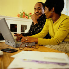 Photograph of a man and a woman looking at a computer