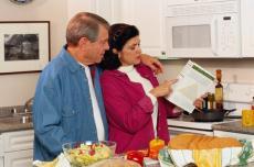 Fotografía de un hombre y una mujer en la cocina leyendo la etiqueta de un alimento