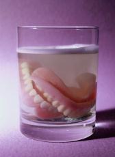 Fotografía de una dentadura postiza en un vaso de líquido