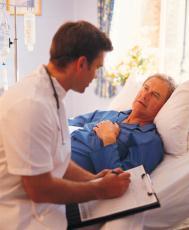 Fotografía de un doctor sentado al lado de la cama de un paciente