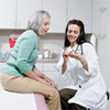 Photograph of a female doctor discussing medication with a female patient