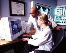 Photograph of a female doctor and a male doctor looking at an MRI scan of a brain