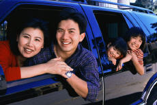 Photograph of a mother, father and young children in an SUV