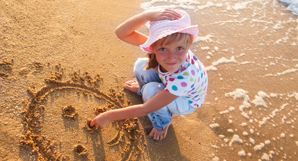 Girl drawing smiley face in beach sand