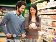 A couple looks at food labels while grocery shopping