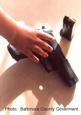 Photograph of a hand reaching for a gun