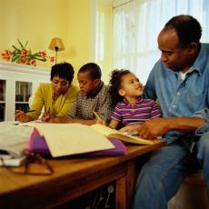 Fotografía de unos padres ayudando a sus dos hijos con las tareas