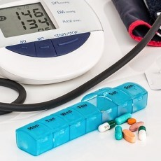 A photograph of pills and a blood pressure machine