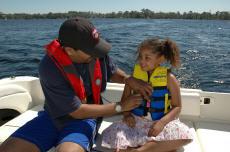 Fotografía de un padre y su hija usando chalecos salvavidas en una lancha