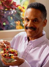 Photograph of a man eating a fruit salad