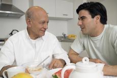 Fotografía de un hombre mayor y un joven hablando mientras desayunan