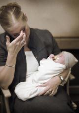 Fotografía de una mujer que aparece disgustada mientras sostiene a su bebé
