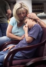 Fotografía de una madre con su hijo que ha sufrido una lesión en la nariz en la sala de espera de un doctor