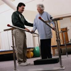 Photograph of a male physical therapist working with an elderly woman
