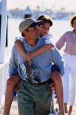 Fotografía de un padre cargando su hijo a caballito