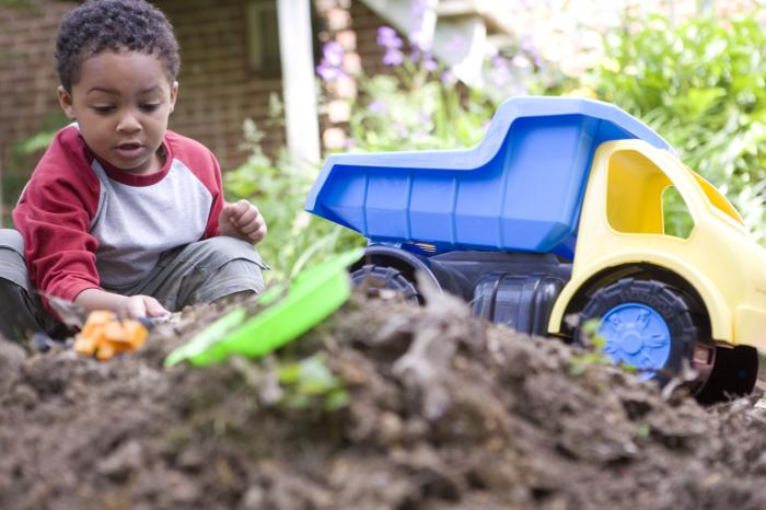 A small child playing with a toy dump truck in a pile of dirt outside of his home