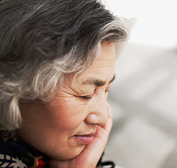 A woman with graying hair has her eyes closed and is resting her head on her hand.