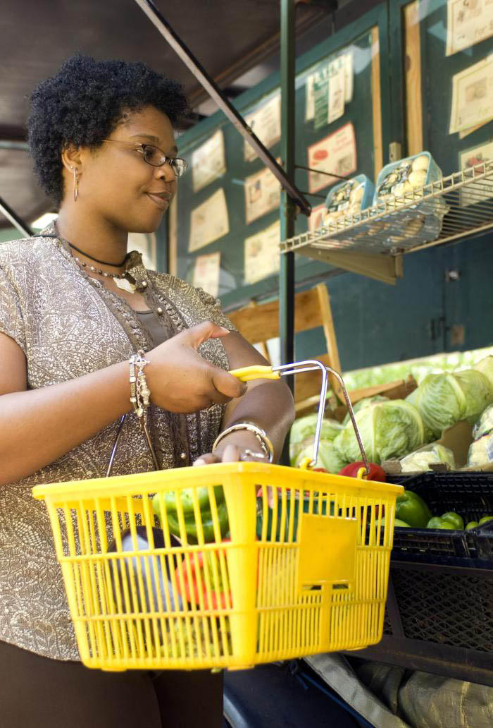A woman is shopping for fresh produce and is placing a green bell pepper into a bright yellow hand-basket that already contains an eggplant and an orange bell pepper