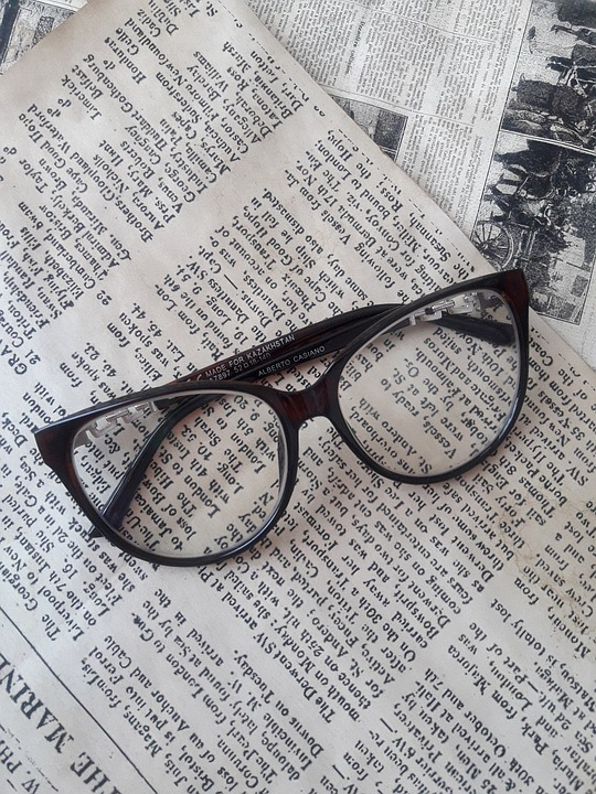 A pair of eyeglasses on top of some newspaper pages