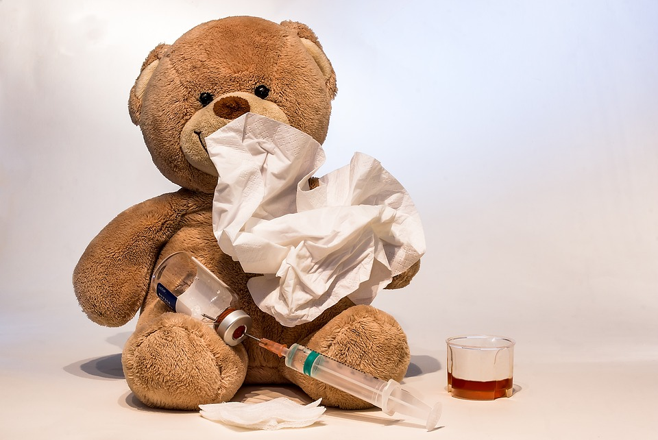 A teddy bear using a paw to hold a tissue up to his mouth and nose, with a vile and syringe in his lap, gauze pads in front of him, and a little medicine cup beside him
