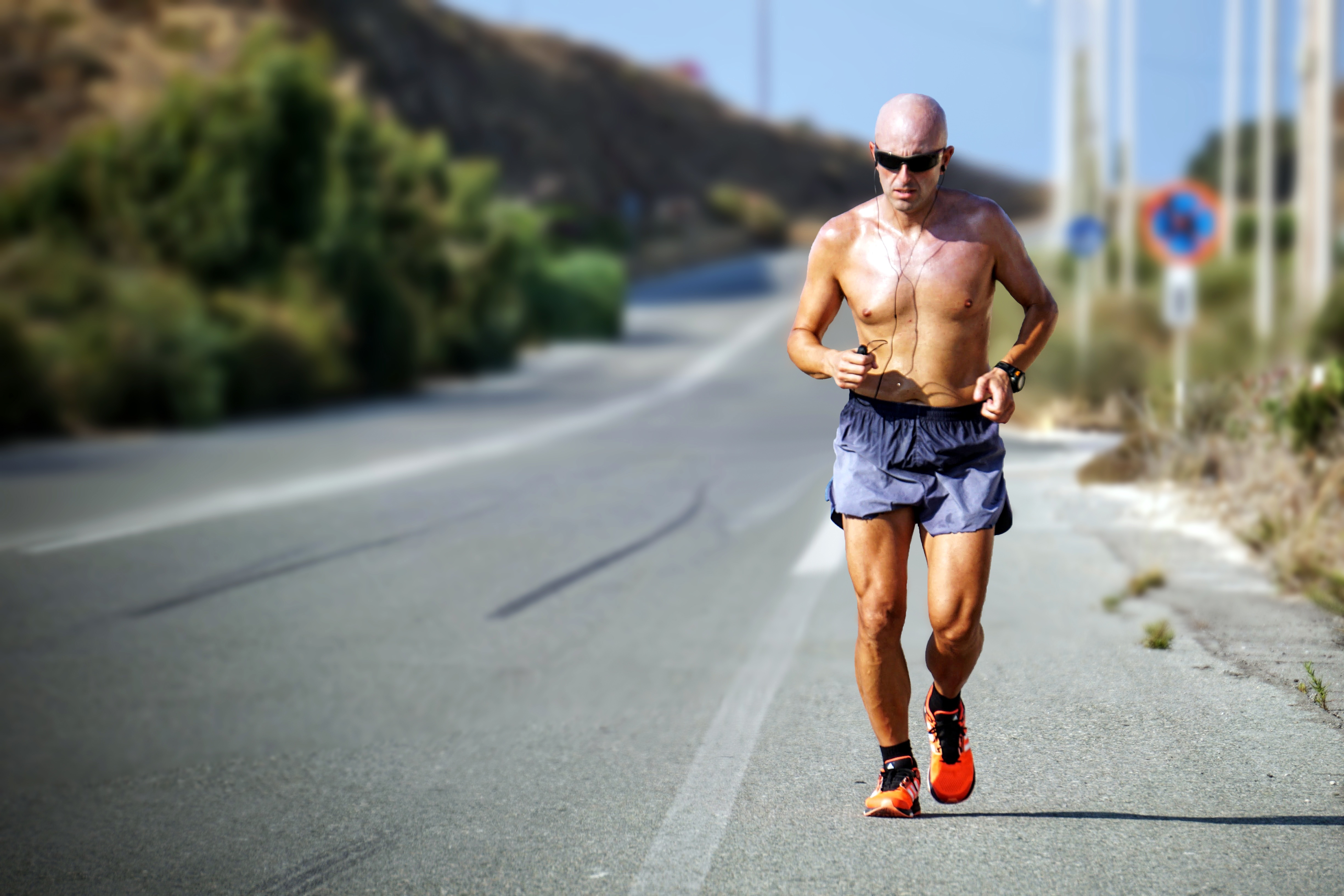 A man is jogging on the shoulder of a road, wearing sunglasses, shorts and tennis shoes.