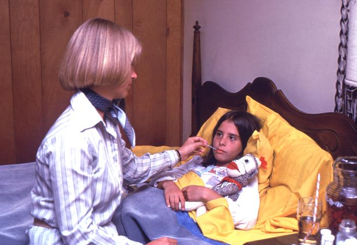 A sick child is in bed with a woman sitting on the bed taking the girl's temperature.