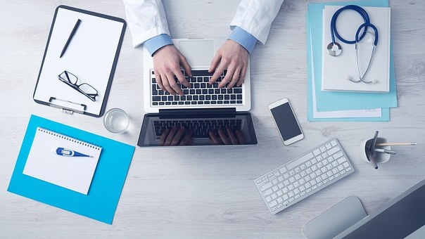 A medical professional is using a laptop in front of a desktop computer, with a mobile phone close by, along with a clipboard with eyeglasses and a pen, a folder with a spiral bound notebook and thermometer on top, papers with a book and stethoscope on top, and a cup of pens and pencils