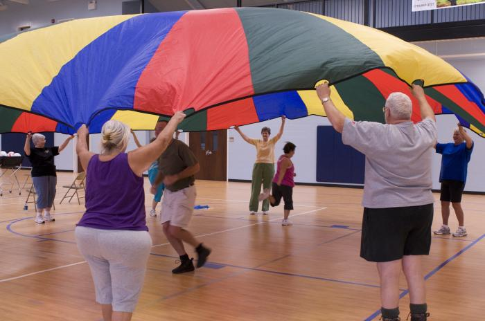 Senior men and women are in a gymnasium doing an activity where their arms are lifted up as they hold onto a parachute, while one man and one woman are running under the parachute.