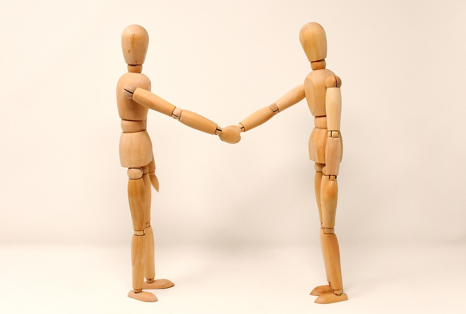 Two carved wooden figures of humans shaking hands