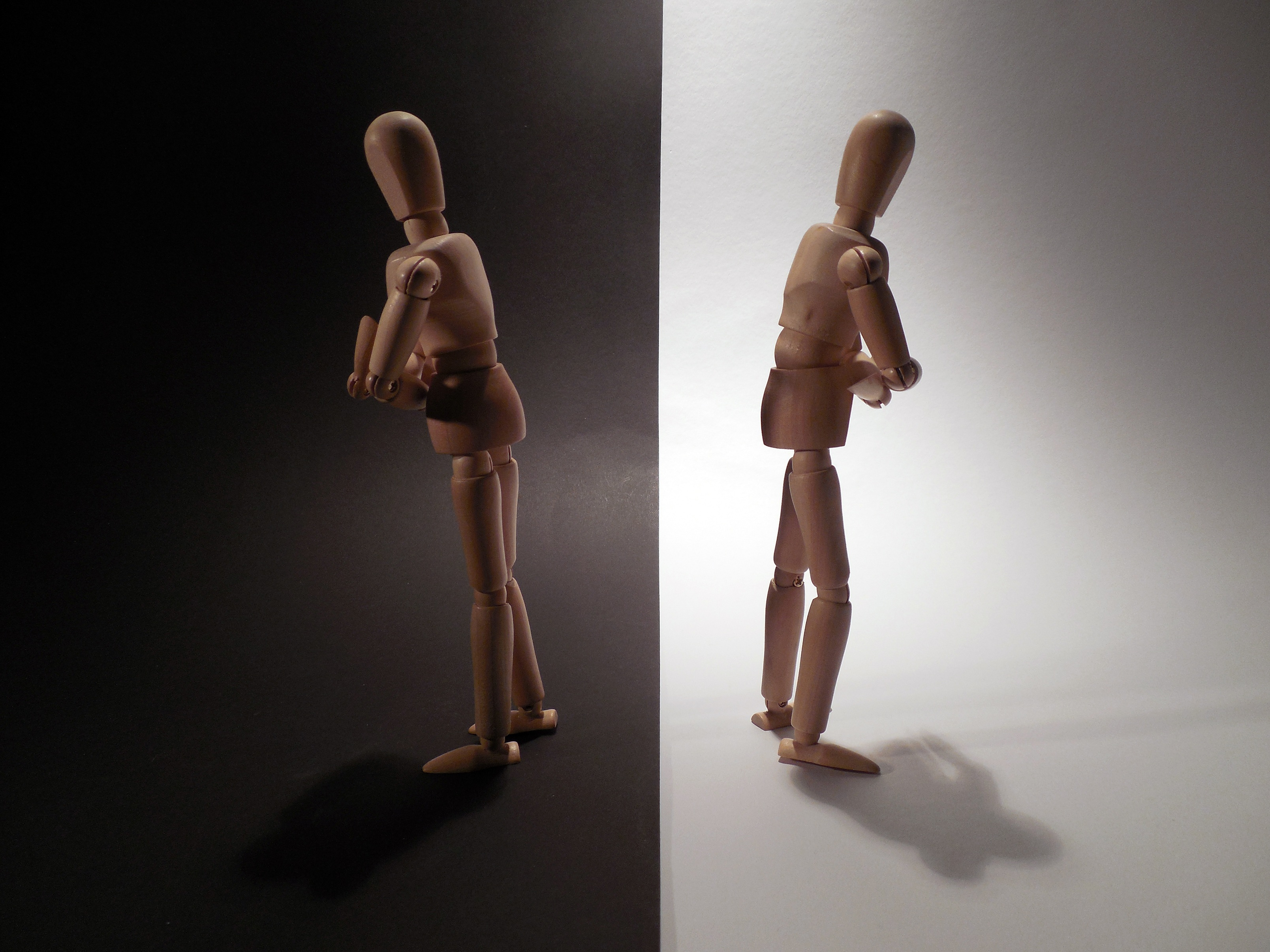 Carved wooden figures of two people with their backs to each other, with the one on the left on a black background facing the left, and the one on the right on a white background facing the right.