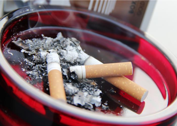 Three cigarettes are left burning in a round red ashtray, with smoke rising from the cigarettes. The cigarettes are almost completely burned down to the ends, and ashes are left behind in the ashtray.