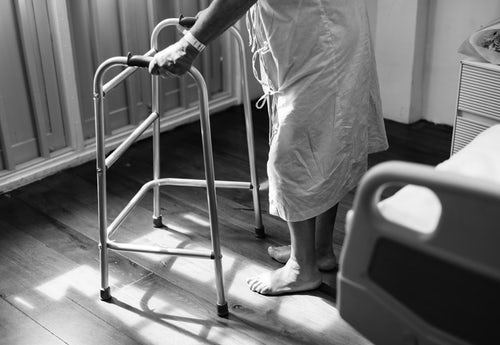 A patient wearing a hospital gown and a hospital identification bracelet is standing beside the hospital bed using a walker