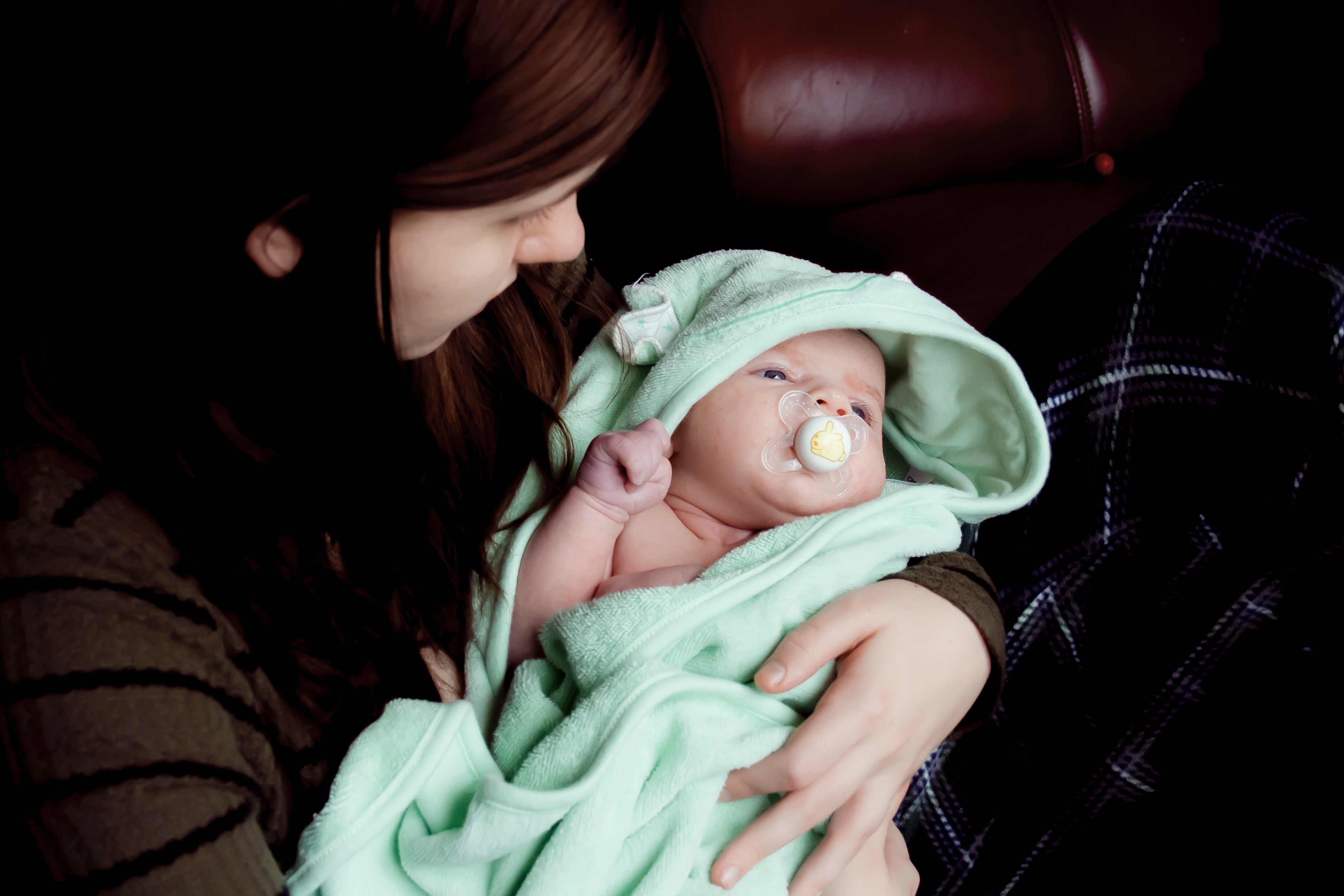A young mother holding her baby who is wrapped in a soft mint green hooded bath towel