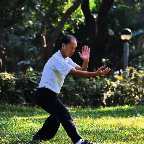 A man practicing Tai Chi outside in the grass with bushes and trees behind him