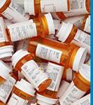 A pile of labeled prescription bottles.