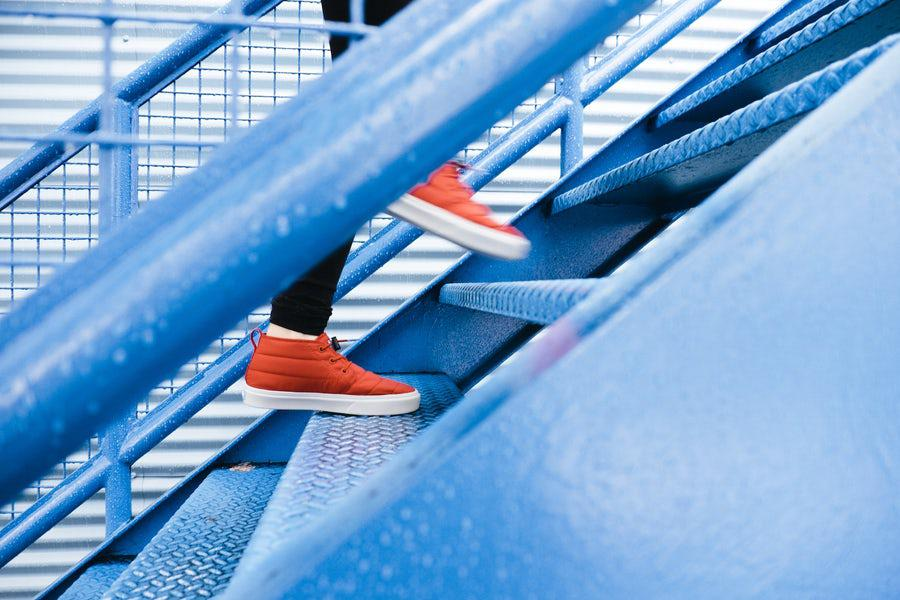 Legs and feet of a woman wearing black leggings and red sneakers, walking up a blue metal staircase