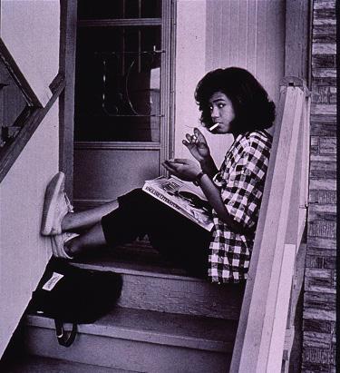 Teenage girl sitting outside on steps lighting a cigarette