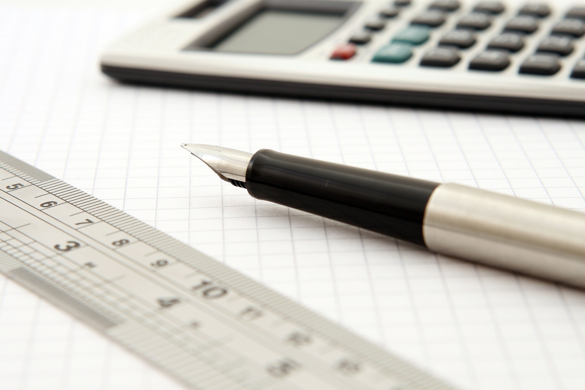 A calculator, a fountain pen, and a ruler on graph paper