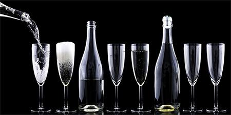 Champagne flutes, some filled and some empty, and filled clear glass bottles lined up with another bottle pouring into the first champagne flute