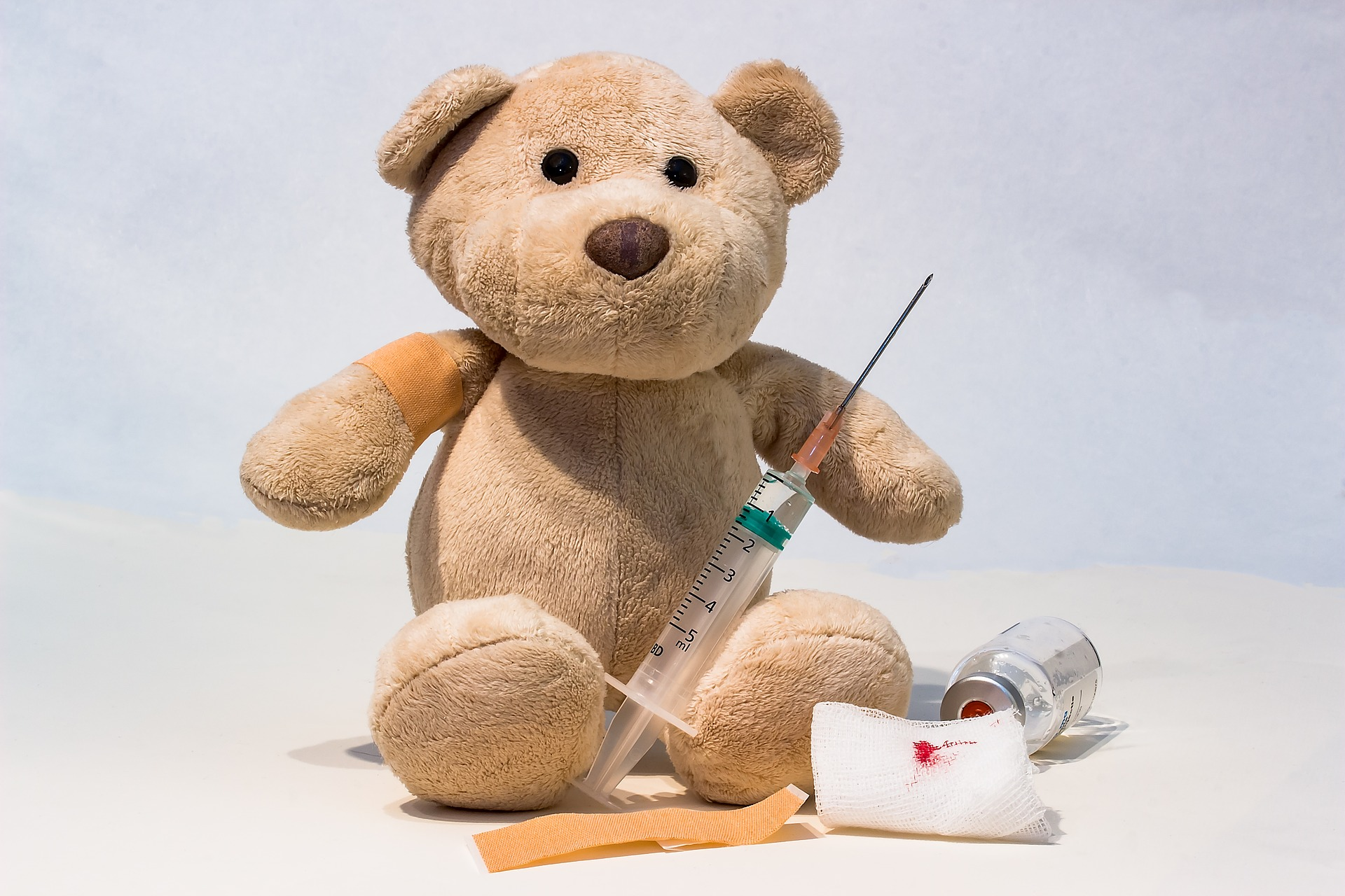 A stuffed bear with a syringe leaning against its left arm, a bandage on its right arm, a bandage in front of the bear, along with a vial and a piece of gauze with blood on it