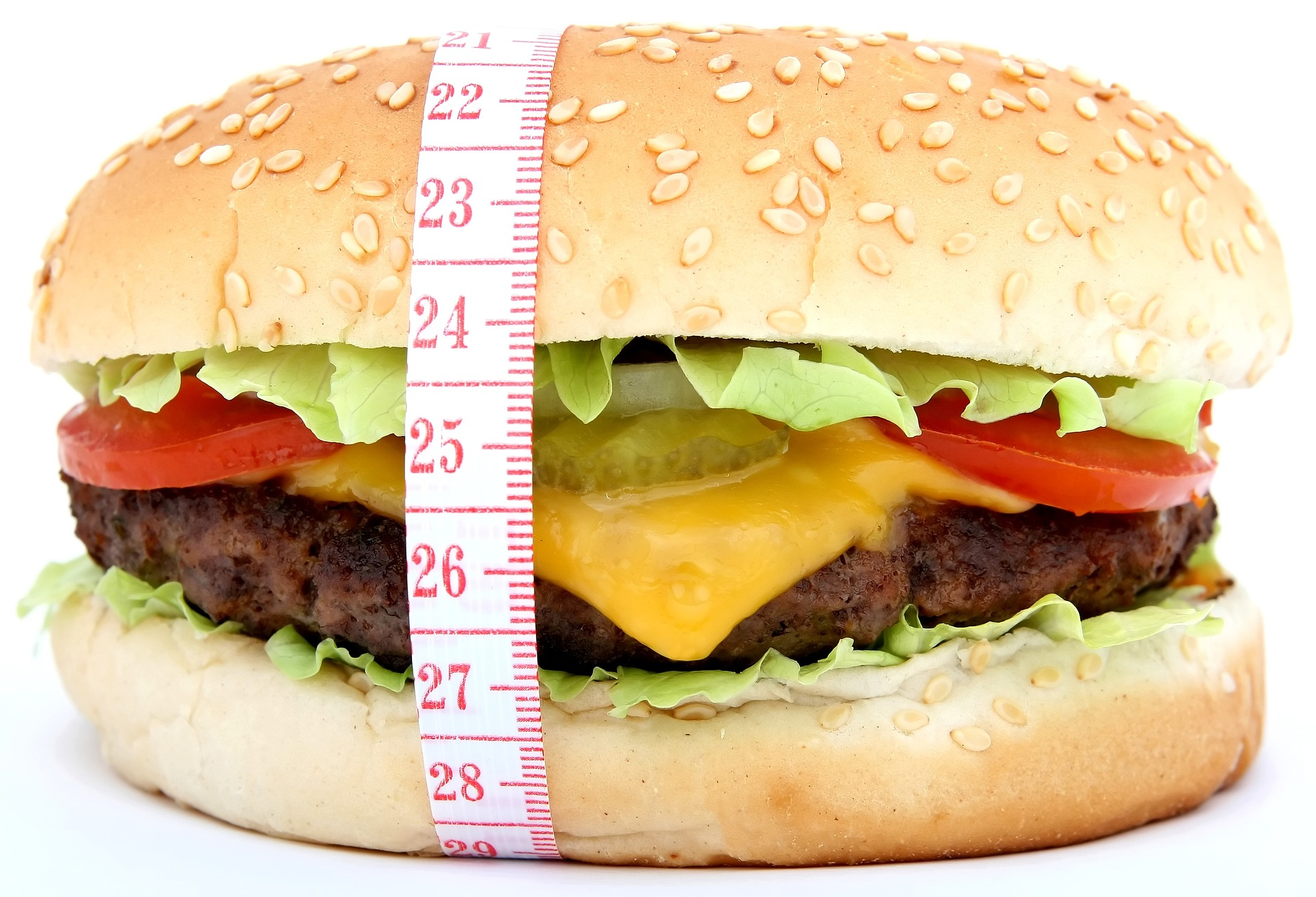 A jumbo hamburger with melted cheese, lettuce, tomato, pickles, and onions on a sesame seed bun with a tape measurer wrapped around it to show that it is very large