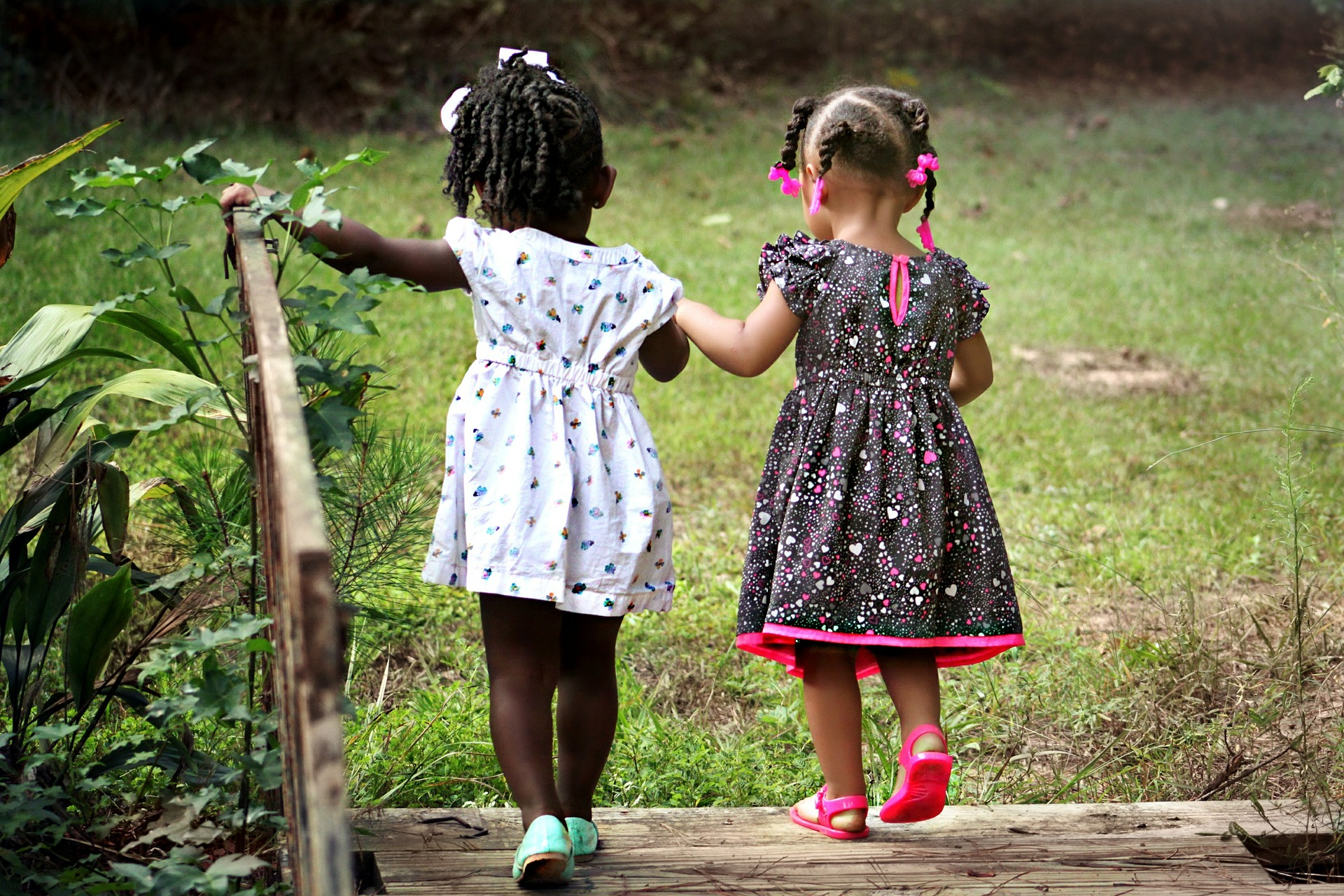 Two little girls, wearing ribbons in their braided hair and summer dresses, are holding hands and stepping off the end of a wooden bridge into a green field